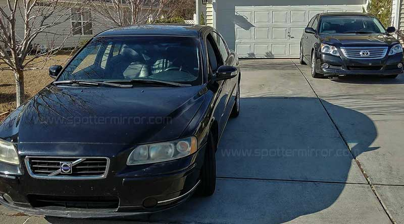 Two cars in a driveway positioned in such a way to demonstrate blind zone