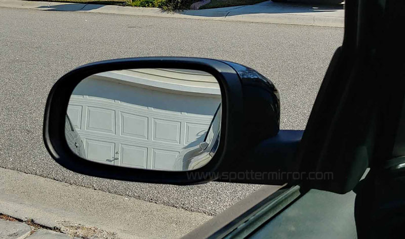 A flat side view mirror with barely visible car